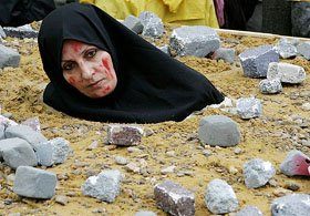 An Iranian woman, dressed up as a victim of death by stoning, takes part in a protest in Brussels